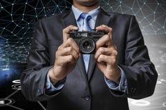 Homem com a câmera nas mãos Imagens de Stock Royalty Free