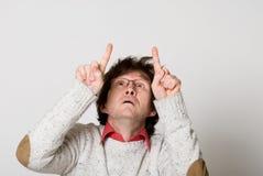 Homem com cabelo disheveled que aponta dois dedos em algo inter Fotografia de Stock Royalty Free