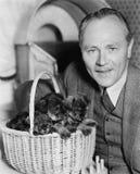 Homem com cachorrinhos em uma cesta (todas as pessoas descritas não são umas vivas mais longo e nenhuma propriedade existe Garant Fotos de Stock Royalty Free