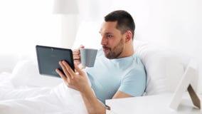 Homem com café bebendo do PC da tabuleta na cama em casa filme