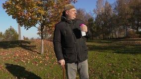 Homem com café da bebida do bastão e passeio no parque video estoque