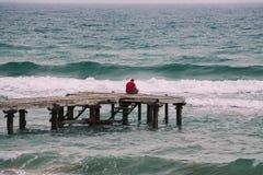 Homem com a camisa vermelha que senta-se apenas em um cais de madeira imagens de stock