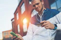 Homem com cartão de crédito e telefone celular que senta-se na rua, no dinheiro da Web e no pagamento em linha, fora fotografia de stock