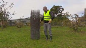 Homem com a cerca de fio no jardim vídeos de arquivo