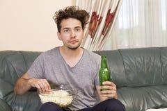 Homem com cerveja e microplaquetas que olham a tevê em casa fotografia de stock royalty free