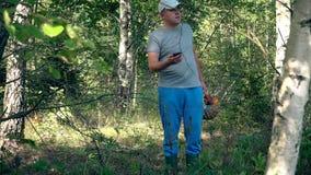 Homem com a cesta completa dos cogumelos que procuram seu sinal de GPS no smartphone