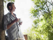Homem com copo de chá que aprecia a vista Imagens de Stock Royalty Free