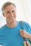 Homem com corda de salto que sorri no health club Imagem de Stock
