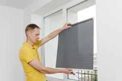 Homem com cortinas de janela Fotos de Stock Royalty Free
