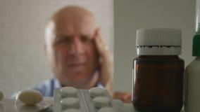 Homem com a dor de cabeça grande que procura comprimidos fotografia de stock royalty free