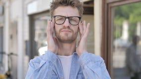 Homem com a dor de cabeça que está exterior vídeos de arquivo
