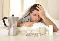 Homem com dor de cabeça e manutenção na cama com tabuletas Imagem de Stock Royalty Free