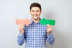 Homem com duas setas que aponta ao direita e esquerdo Imagem de Stock