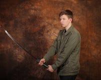 Homem com a espada do katana no fundo marrom do batik Fotos de Stock Royalty Free