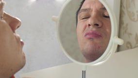 Homem com espinhas em uma parte dianteira do espelho video estoque