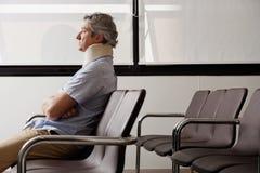 Homem com ferimento do pescoço que espera na entrada fotografia de stock royalty free