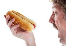 Homem com fome com cão quente Imagem de Stock