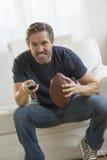 Homem com futebol americano que olha a tevê Imagem de Stock Royalty Free
