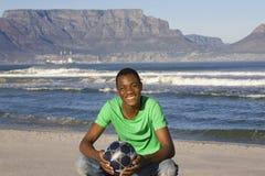 Homem com futebol na praia da montanha da tabela Fotos de Stock