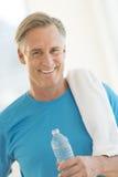 Homem com garrafa de água e toalha no Gym Fotografia de Stock