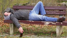 Homem com garrafa de cerveja que dorme em um banco no parque vídeos de arquivo