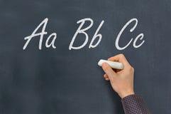Homem com giz que escreve letras de ABC no quadro-negro Fotos de Stock Royalty Free