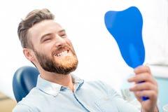 Homem com grande sorriso no escritório dental fotografia de stock royalty free