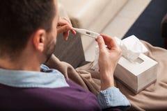 Homem com a gripe que lê um termômetro Fotografia de Stock Royalty Free
