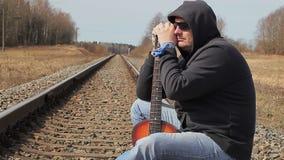 Homem com a guitarra na estrada de ferro vídeos de arquivo