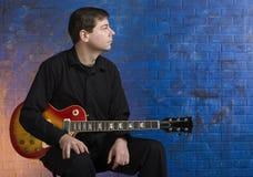 Homem com a guitarra no regaço imagem de stock