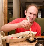 Homem com jogo de rolos de sushi Fotografia de Stock Royalty Free