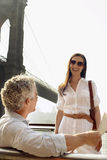 Homem com jornal que fala à mulher pela ponte de Brooklyn Fotografia de Stock