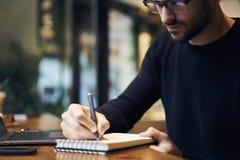 Homem com a leitura do telefone celular que nota ideias no organizador antes de datilografar no portátil foto de stock