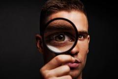 Homem com lente de aumento fotografia de stock royalty free