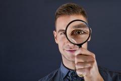 Homem com lente de aumento imagem de stock
