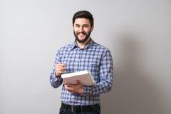 Homem com livro de texto Imagens de Stock