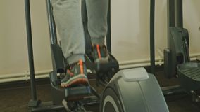 Homem com a máquina elíptica no gym