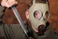 Homem com máscara de gás e espada do katana no fundo marrom do batik Foto de Stock Royalty Free