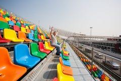 Homem com mãos acima nos assentos para espectadores Imagem de Stock Royalty Free