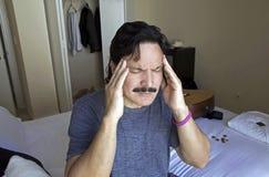 Homem com mãos ao templo no sinal da dor ou da aflição Foto de Stock Royalty Free