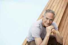 Homem com mãos em Chin Relaxing By Pool Imagem de Stock Royalty Free