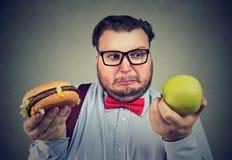 Homem com a maçã e o hamburguer que olham confundidos Imagens de Stock