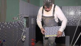 Homem com medida da telha da ferramenta e do marcador do medidor e para fazer marcas na telha cerâmica da parede vídeos de arquivo
