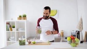 Homem com misturador que cozinha a cozinha do batido em casa filme