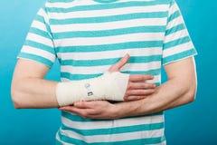 Homem com mão enfaixada dolorosa Foto de Stock