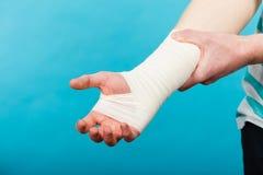 Homem com mão enfaixada dolorosa Fotos de Stock Royalty Free