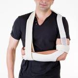 Homem com o braço apoiado no estilingue no estúdio branco Imagem de Stock