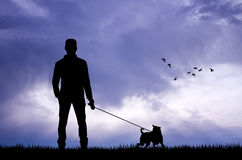 Homem com o cão no por do sol Fotos de Stock