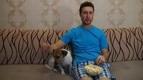 Homem com o cão que olha a tevê vídeos de arquivo