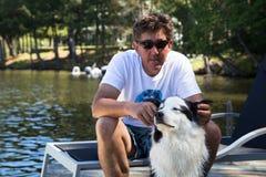 Homem com o cão satisfeito na doca Foto de Stock Royalty Free